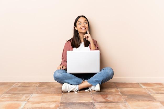 Mulher jovem mestiça com um laptop sentada no chão pensando em uma ideia enquanto olha para cima