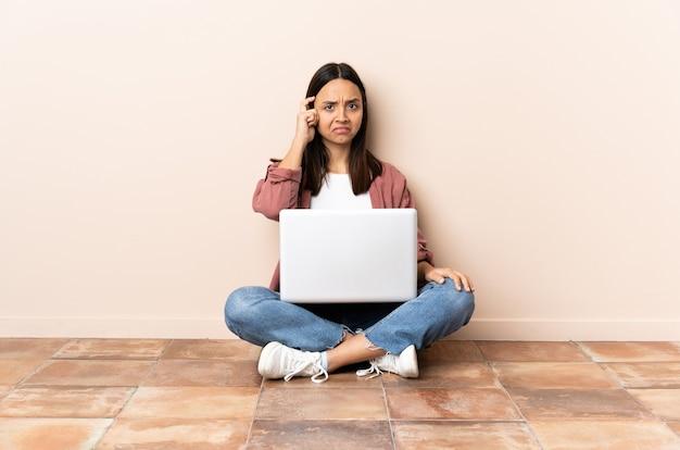 Mulher jovem mestiça com um laptop sentada no chão pensando uma ideia