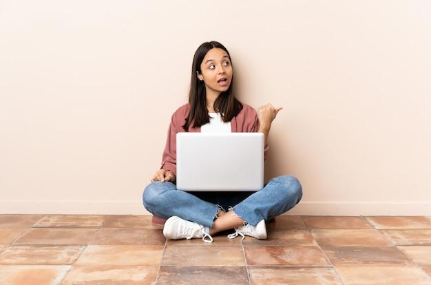 Mulher jovem mestiça com um laptop sentada no chão