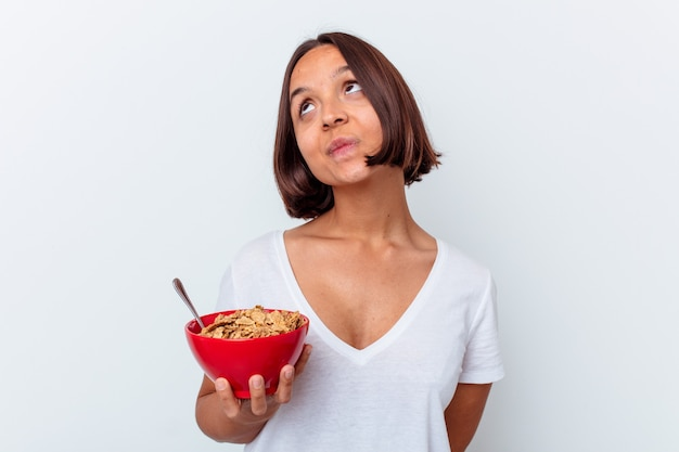 Mulher jovem, mestiça, comendo cereais isolados no fundo branco, sonhando em alcançar objetivos e propósitos