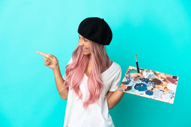 Mulher jovem mestiça de cabelo rosa segurando uma paleta isolada em um fundo azul apontando o dedo para o lado e apresentando um produto