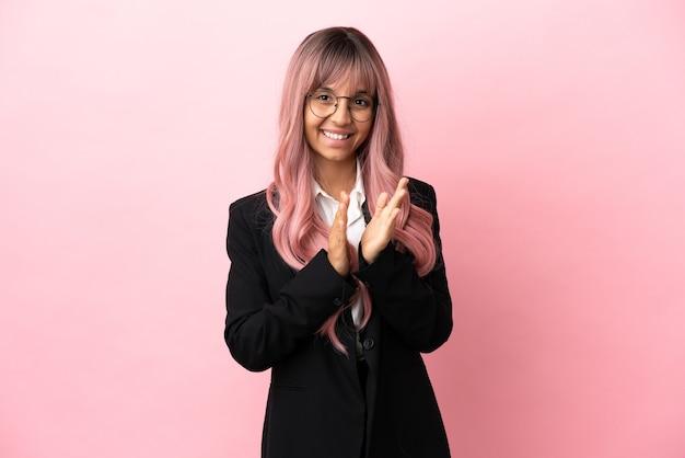 Mulher jovem mestiça de negócios com cabelo rosa isolada em um fundo rosa aplaudindo após apresentação em uma conferência