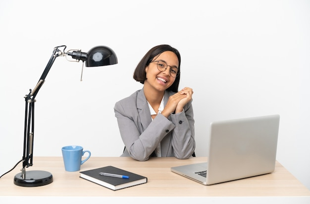 Mulher jovem, mestiça de negócios, trabalhando no escritório, aplaudindo