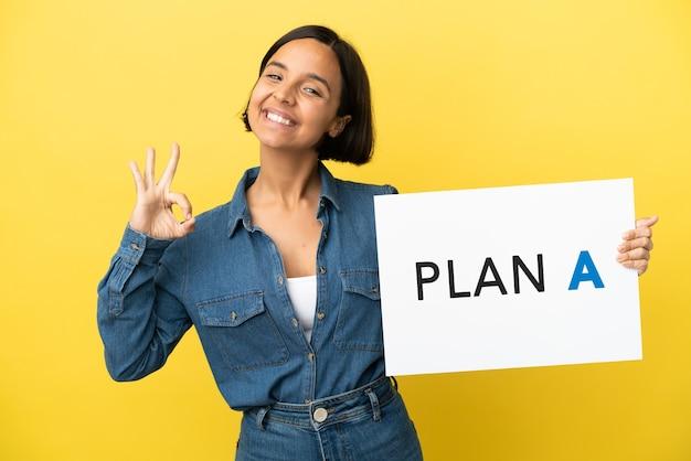 Mulher jovem mestiça isolada em fundo amarelo segurando um cartaz com a mensagem plano a com o sinal de ok