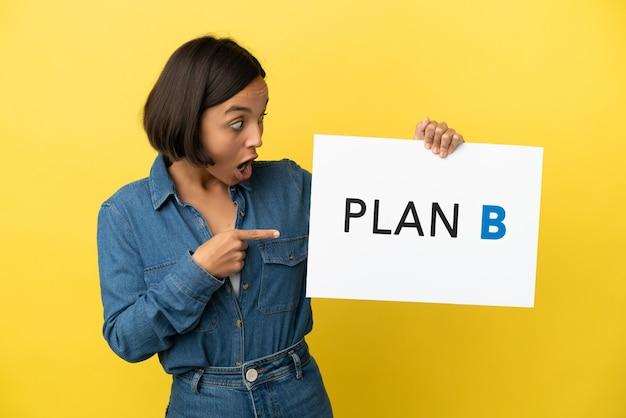 Mulher jovem mestiça isolada em fundo amarelo segurando um cartaz com a mensagem plano b com expressão de surpresa