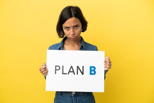 Mulher jovem mestiça isolada em fundo amarelo segurando um cartaz com a mensagem plano b com expressão triste