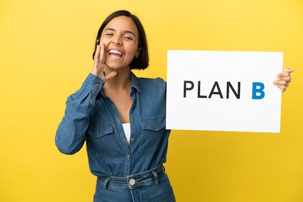 Mulher jovem mestiça isolada em fundo amarelo segurando um cartaz com a mensagem plano b e gritando