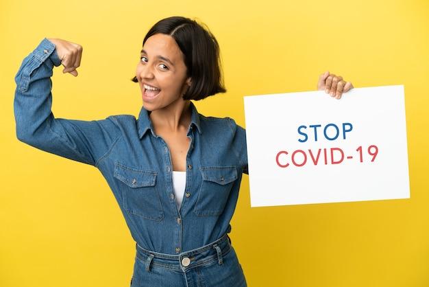 Mulher jovem mestiça isolada em fundo amarelo segurando um cartaz com o texto pare covid 19 e fazendo um gesto forte
