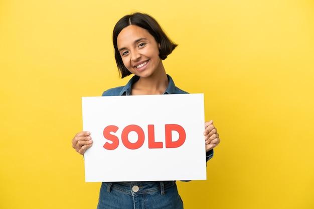 Mulher jovem mestiça isolada em fundo amarelo segurando um cartaz com o texto vendido com expressão feliz