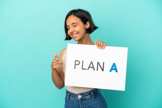 Mulher jovem mestiça isolada em fundo azul segurando um cartaz com a mensagem plano a apontando para a frente
