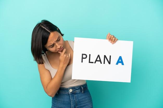 Mulher jovem mestiça isolada em fundo azul segurando um cartaz com a mensagem plano a e pensando