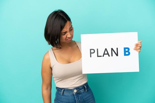 Mulher jovem mestiça isolada em fundo azul segurando um cartaz com a mensagem plano b com expressão triste