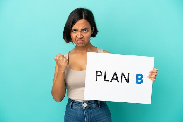 Mulher jovem mestiça isolada em fundo azul segurando um cartaz com a mensagem plano b e zangada