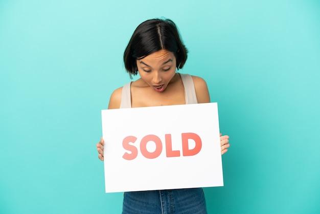 Mulher jovem mestiça isolada em fundo azul segurando um cartaz com o texto vendido com expressão de surpresa