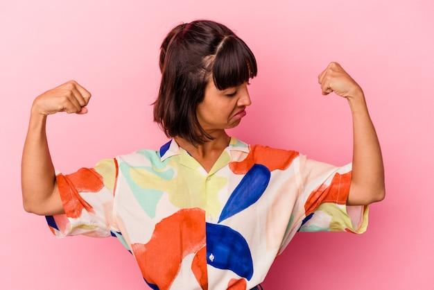 Mulher jovem mestiça isolada em fundo rosa mostrando gesto de força com os braços, símbolo do poder feminino