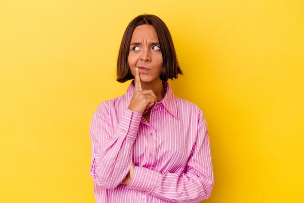 Mulher jovem mestiça isolada em um fundo amarelo, contemplando, planejando uma estratégia, pensando no caminho de um negócio.