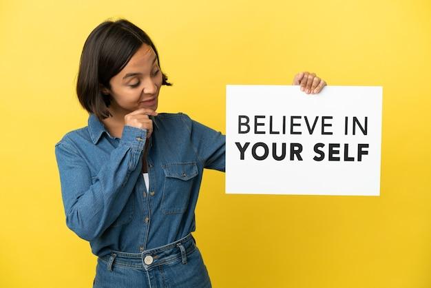 Mulher jovem mestiça isolada em um fundo amarelo segurando um cartaz com o texto acredite em si mesmo e pensando