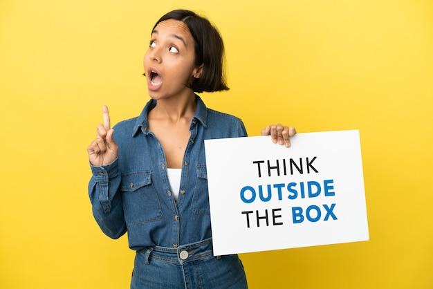 Mulher jovem mestiça isolada em um fundo amarelo segurando um cartaz com o texto pense fora da caixa e pensando