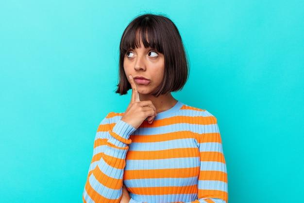 Mulher jovem mestiça isolada em um fundo azul, contemplando, planejando uma estratégia, pensando no funcionamento de um negócio.