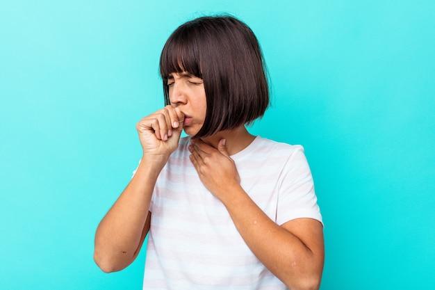 Mulher jovem, mestiça, isolada em um fundo azul, sofre de dor na garganta devido a um vírus ou infecção.