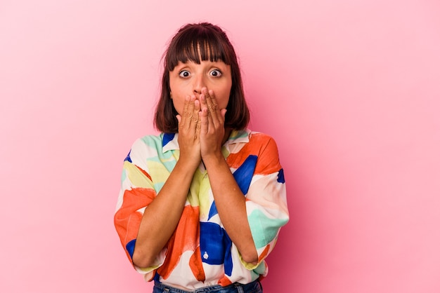 Mulher jovem mestiça isolada em um fundo rosa chocada, cobrindo a boca com as mãos, ansiosa para descobrir algo novo.
