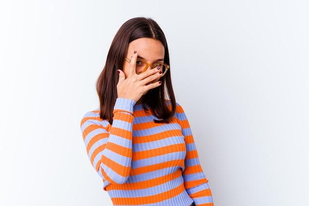 Mulher jovem mestiça isolada piscar para a câmera por entre os dedos, rosto cobrindo vergonha.