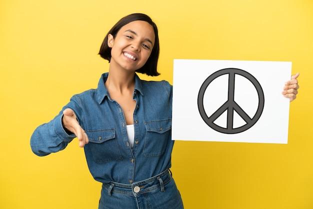 Mulher jovem mestiça isolada segurando um cartaz com o símbolo da paz fazendo um acordo