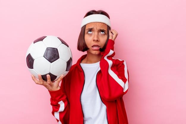 Mulher jovem, mestiça, jogando futebol, isolada na parede rosa, em choque, lembrou-se de um encontro importante