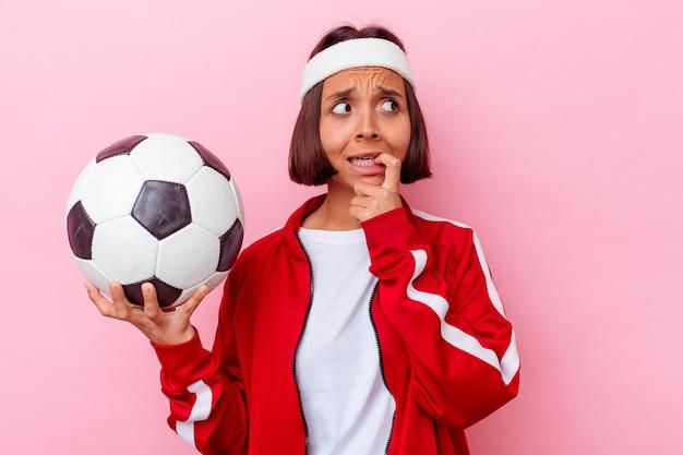 Mulher jovem mestiça jogando futebol isolada na parede rosa, roendo as unhas, nervosa e muito ansiosa.