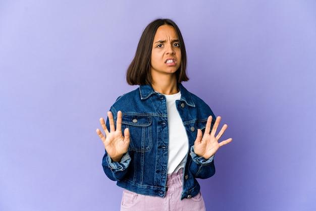 Mulher jovem mestiça rejeitando alguém com um gesto de nojo.