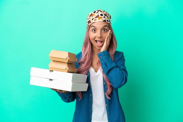 Mulher jovem mestiça segurando pizzas e hambúrgueres isolados em um fundo verde com expressão facial surpresa e chocada