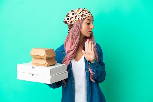 Mulher jovem mestiça segurando pizzas e hambúrgueres isolados em um fundo verde fazendo gesto de pare e decepcionada