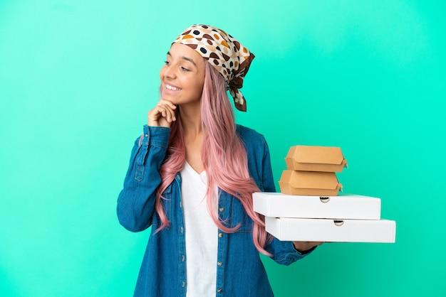 Mulher jovem mestiça segurando pizzas e hambúrgueres isolados em um fundo verde, olhando para o lado e sorrindo