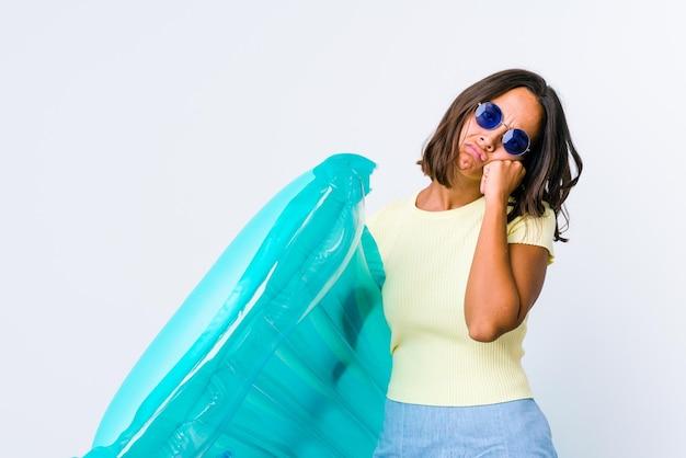 Mulher jovem mestiça segurando um colchão de ar, cansada de uma tarefa repetitiva.