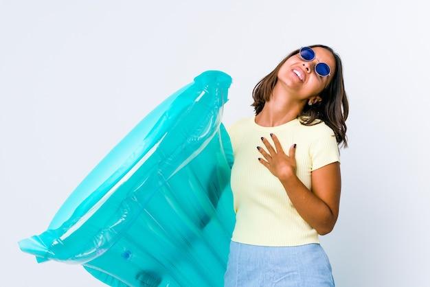 Mulher jovem mestiça segurando um colchão de ar tem uma expressão amigável, pressionando a palma da mão no peito. conceito de amor.