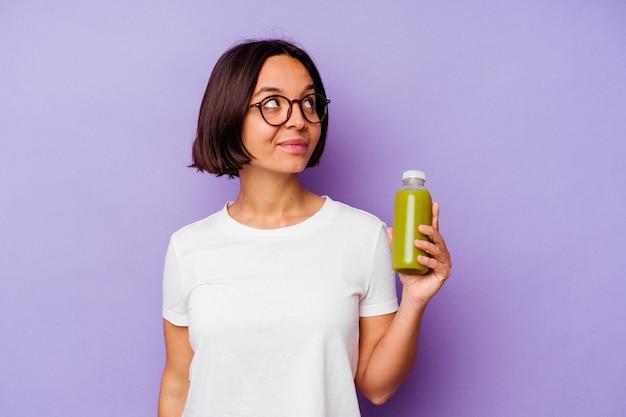 Mulher jovem mestiça segurando um smoothie saudável isolado no fundo roxo e sonhando em alcançar objetivos e propósitos