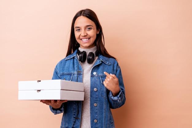Mulher jovem mestiça segurando uma pizza isolada pessoa apontando com a mão para um espaço de cópia de camisa, orgulhosa e confiante