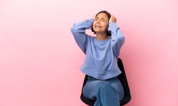 Mulher jovem mestiça sentada em uma cadeira isolada em um fundo rosa estressada oprimida