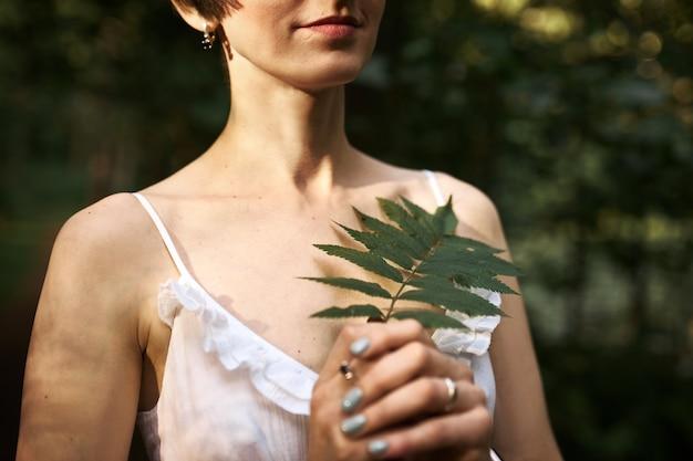 Mulher jovem misteriosa irreconhecível com penteado curto e pele pálida, caminhando na floresta sozinha, segurando uma folha de samambaia verde.