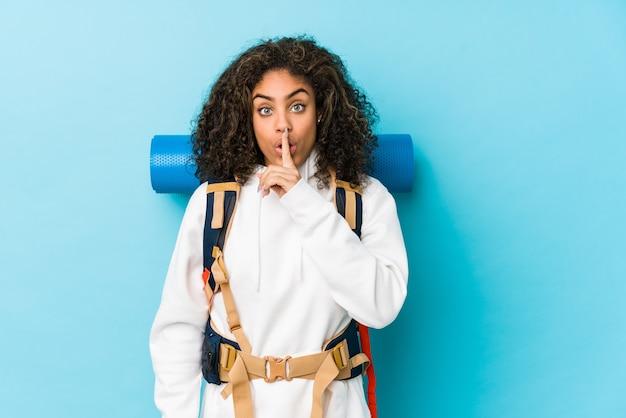 Mulher jovem mochileiro afro-americana, mantendo um segredo ou pedindo silêncio.