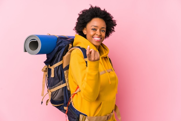Mulher jovem mochileiro americano africano isolado apontando com o dedo para você, como se convidando se aproximar.