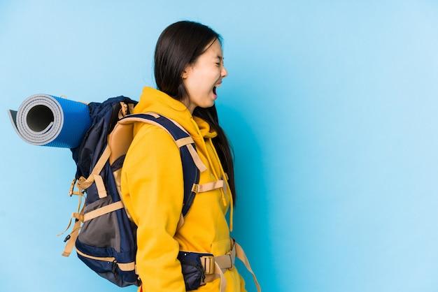 Mulher jovem mochileiro chinês isolado gritando para um espaço de cópia