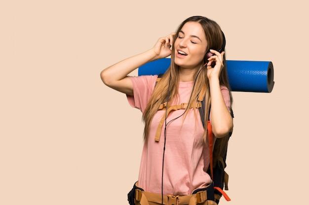 Mulher jovem mochileiro ouvindo música com fones de ouvido na parede amarela isolada