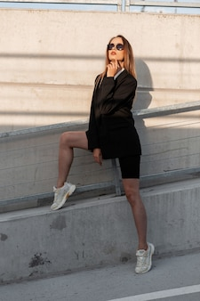 Mulher jovem moda legal em óculos de sol vintage na camisa branca na moda na jaqueta preta na moda em tênis perto da parede na cidade ao pôr do sol brilhante. menina moderna elegante em roupas casuais de jovens na rua.