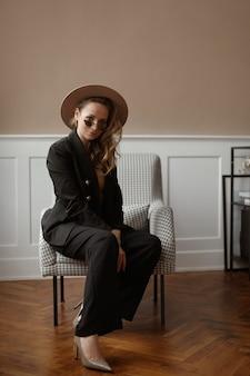 Mulher jovem modelo com maquiagem suave, usando chapéu da moda e óculos de sol da moda, sentado em um vintage.