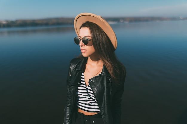Mulher jovem modelo posando em um dia de outono na orla do lago, vestida com roupas casuais