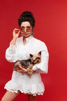 Mulher jovem modelo usando óculos escuros da moda e vestido branco mantém um yorkshire terrier em seu ... Foto Premium