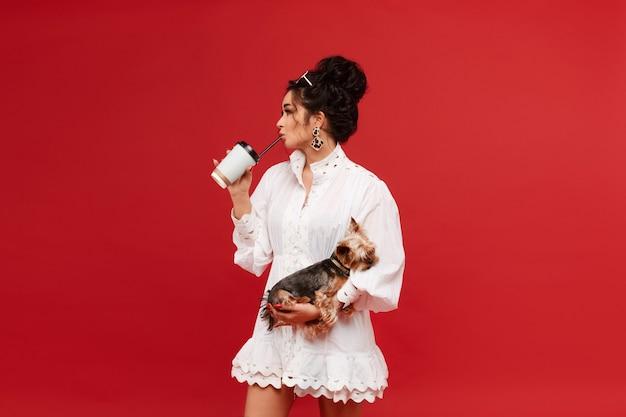 Mulher jovem modelo usando óculos escuros da moda e vestido branco mantém um yorkshire terrier em seu ...