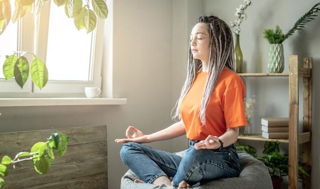 Mulher jovem moderna está sentada em uma cadeira larga pela manhã em casa e meditando