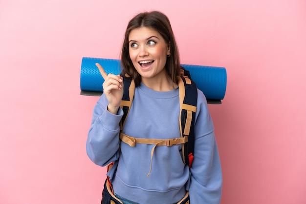 Mulher jovem montanhista isolada com uma grande mochila tentando descobrir a solução enquanto levanta um dedo